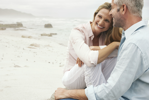 middle-aged couple smiling and hugging on the beach